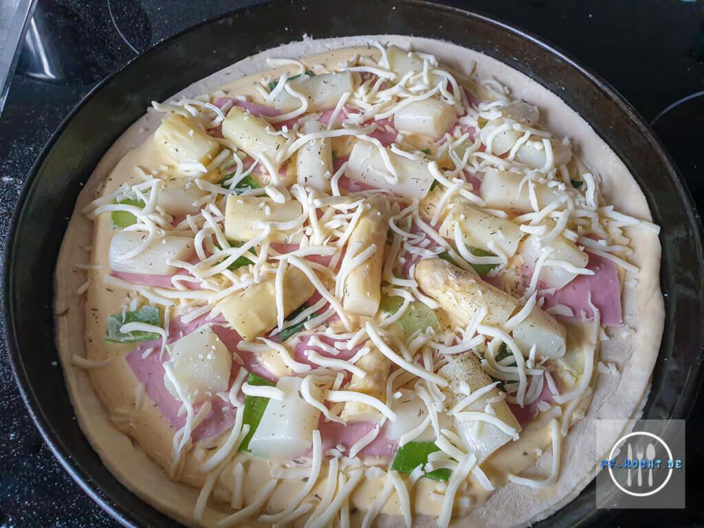 Spargelpizza mit Sauce Hollandaise bereit für den Backofen
